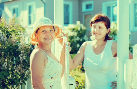 caller: Two happy women near fence wicket. Selective focus on left woman Stock Photo