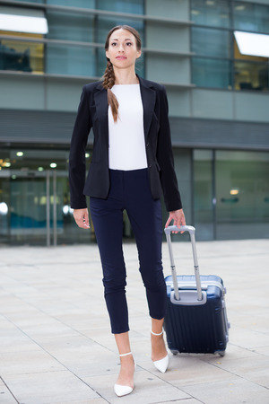 Businesswoman in suit with suitcase is staying near the building of airport. Stock Photo