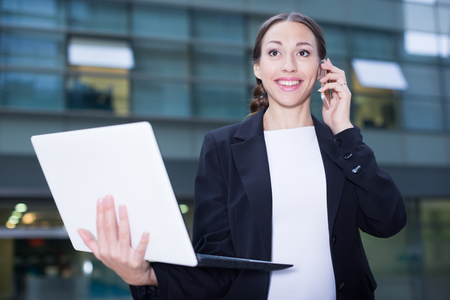 Businesswoman is happy after agreed about the successful transaction by phone outdoors.
