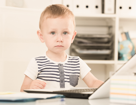 Cute boy is playing on laptop in the office.