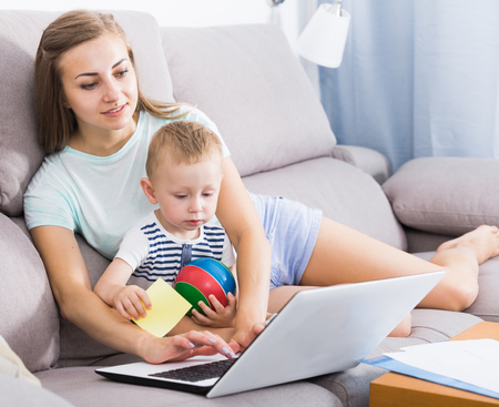 Satisfied mother with kid is productively working behind laptop at home.