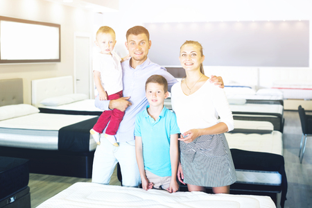 Young happy family of four posing together in modern home furnishings store