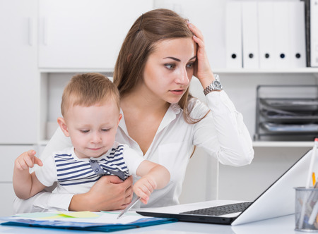 Perplexed mother with kid is having issue while working behind laptop in office. Stock Photo