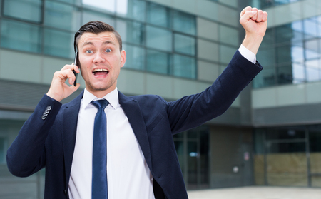 Office manager is happy after agreed about the successful transaction by phone outdoors.