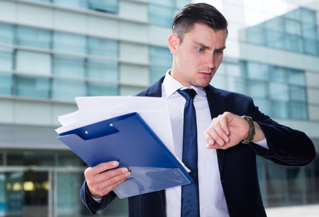Businessman is looking on watch near the office and understand that he late. Stock Photo