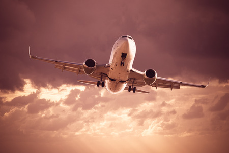 White jet plane flying in troubled cloudy sky Stock Photo