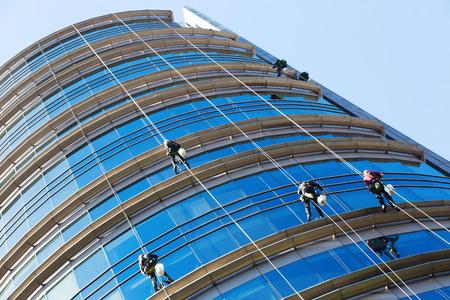 Grupo de alpinistas industriales lavando ventanas de rascacielos Foto de archivo - 88090906