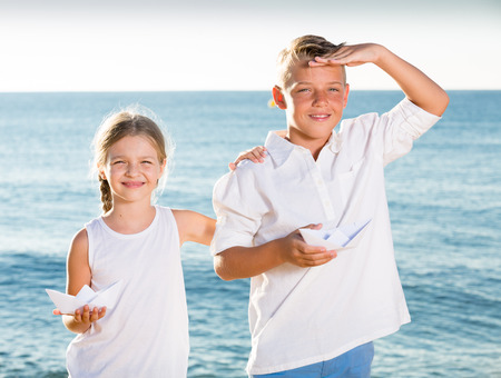 portrait of smiling boy and girl standing and holding paper boat toys in hands on beach