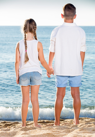 boy and girl in elementary school age sitting together on beach with back forward
