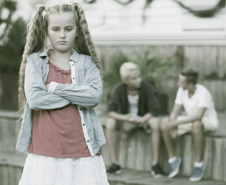 Upset girl offended after quarrel with playmates outside Stock Photo