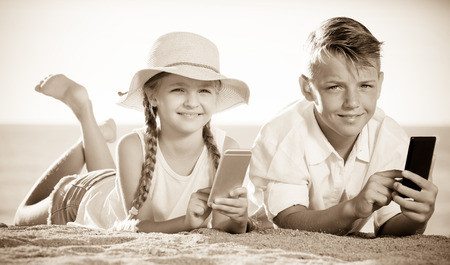 Portrait of two positive children in elementary school age on beach with phone in hands