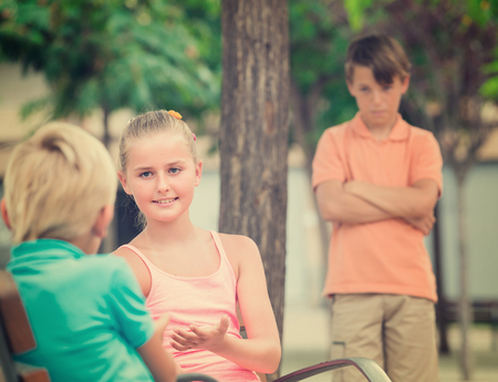 argue kid: Girl is talking with boy in the distance from their offended friend.