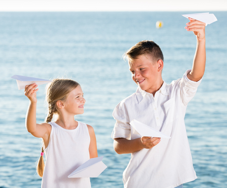 niños platicando: happy two kids in elementary school playing together with origami airplane toys on beach Foto de archivo