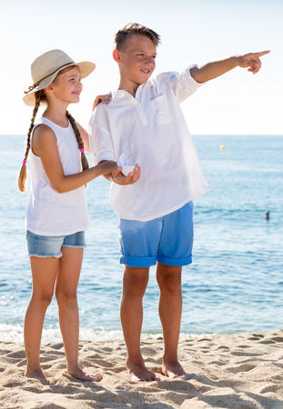 two cheerful kids pointing with fingers aside on sandy beach on sunny weather