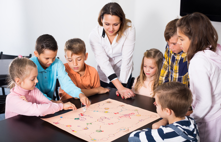 Woman and happy children sitting at table with board game and dice in school