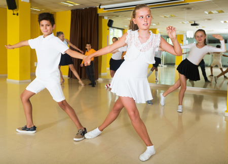 Children in dance hall learning new movements, smiling and having fun Stock Photo