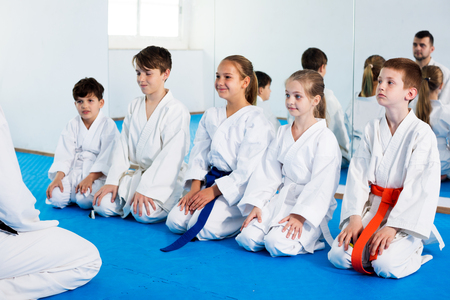 Cheerful children enjoying their trainings with coach at karate class Stock Photo