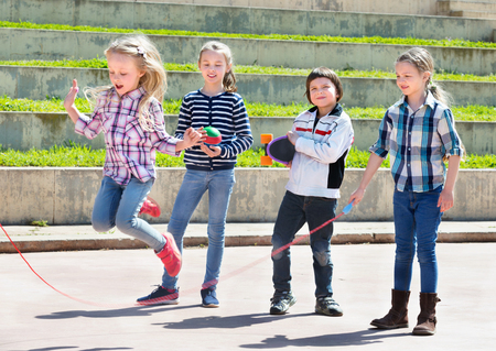 Happy children playing skipping rope jumping game and laughing outdoors