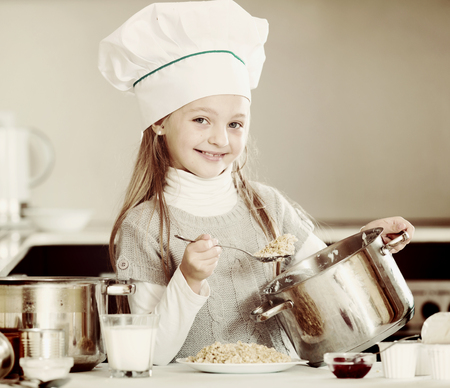 Little girl cooking tasty and healthy porridge in kitchen Stock Photo