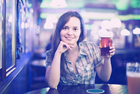 Sexy girl sits in bar with beer glass