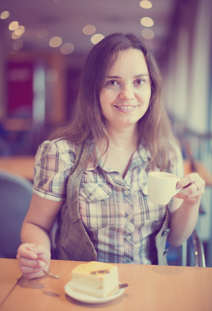 Young girl drinking morning coffee in cafe