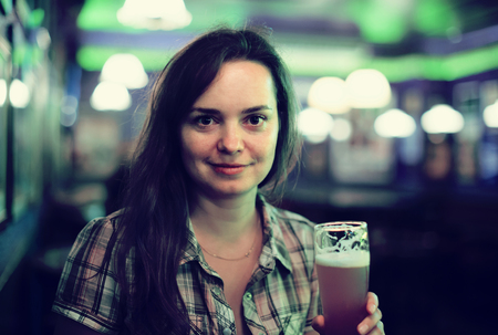 smiling girl sits in bar with beer glass Stock Photo
