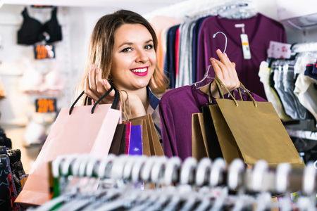 Smiling glad  friendly female shopper boasting her purchases in underwear shop Stock Photo