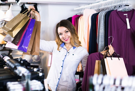Smiling woman is enjoying her purchases in wear shop. Stock Photo