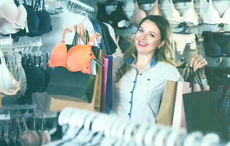 boasting: Woman is enjoying her purchases in underwear shop. Stock Photo