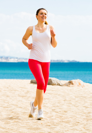Smiling young girl running on beach by sea at daytime Stock Photo