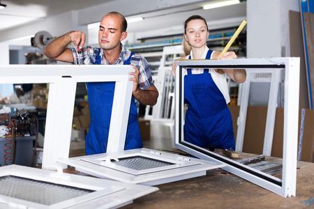 Homme positif et une fille dans une combinaison bleue assembler des fenêtres en plastique à l'usine Banque d'images
