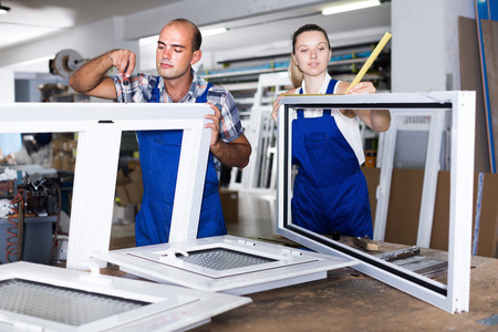 Positive man and girl in blue overalls assembling plastic windows at factory Stock Photo