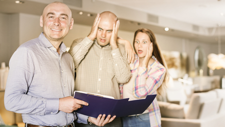 astonishing: Smiling furniture salesman on background with couple shocked by prices