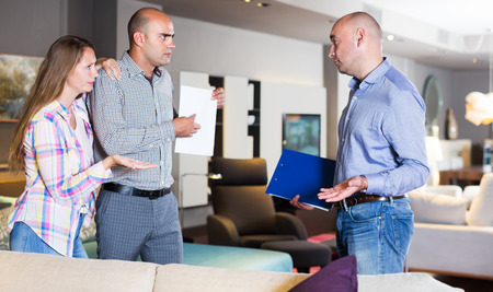 Disgruntled married couple communicating with furniture seller about poor-quality service. Focus on woman Stock Photo