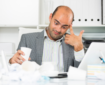 Busy businessman in shirt worrying at the computer with cup of water