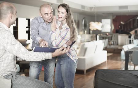 Erwachsene überraschte und entsetzte Paare, die Preisliste im Einrichtungsspeicher überwachen Standard-Bild - 88194771