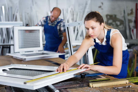 profile measurement: Young diligent efficient  female worker measuring finished metal-plastic window in workshop Stock Photo