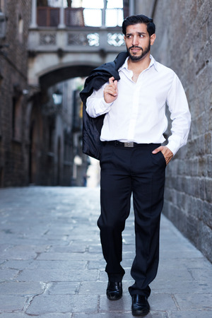 dressy: Confident young man in formal clothes strolling past old stone castle