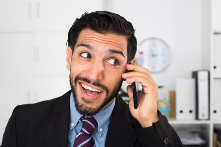 dispatcher: Spanish businessman is excited while talking phone in office.
