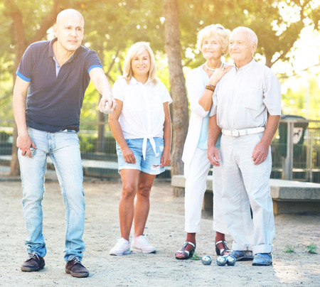Happy cheerful  smiling family playing petanque in outdoor Stock Photo