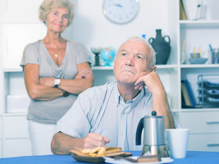 Elderly upset man sitting separately having problems in relationship with spouse