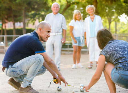 Glad pleasant smiling family playing petanque in outdoor