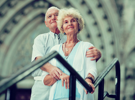 Portrait of loving mature spouses standing near an iron handrails and ancient cathedral Stock Photo