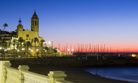 Sunset view of Sitges.  Church of Sant Bartomeu i Santa Tecla at beach. Catalonia Stock Photo