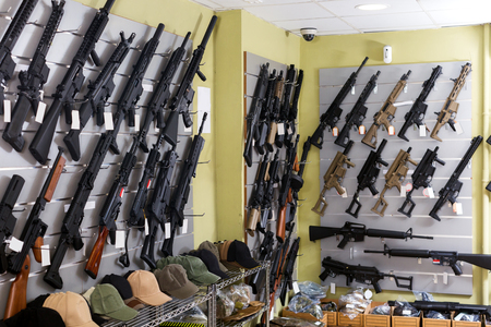 Guns hangs on the wall in military store closeup 스톡 콘텐츠