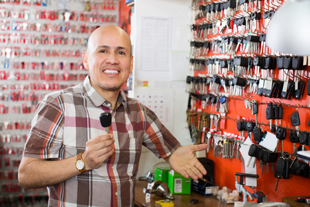 Mature smiling key cutter near stand with auto keys in locksmith