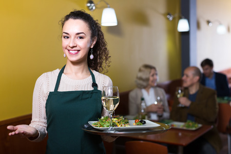 ensaladilla rusa: Portrait of waitress working in ordinary restaurant and holding tray
