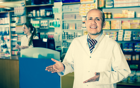 Cheerful pharmacist standing at pay desk and pharmacy technician helping