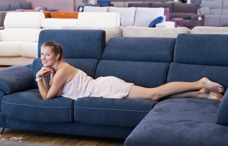 Adult female customer barefoot lying on sofa in the furniture store