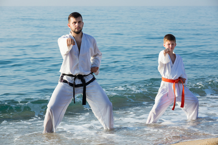 Male coach and boy in uniform practising karate poses at sunny sea shore